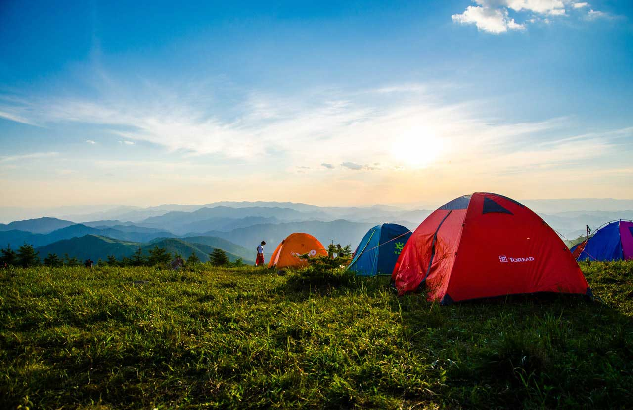 Photo of Pitched Dome Tents Overlooking Mountain Ranges.