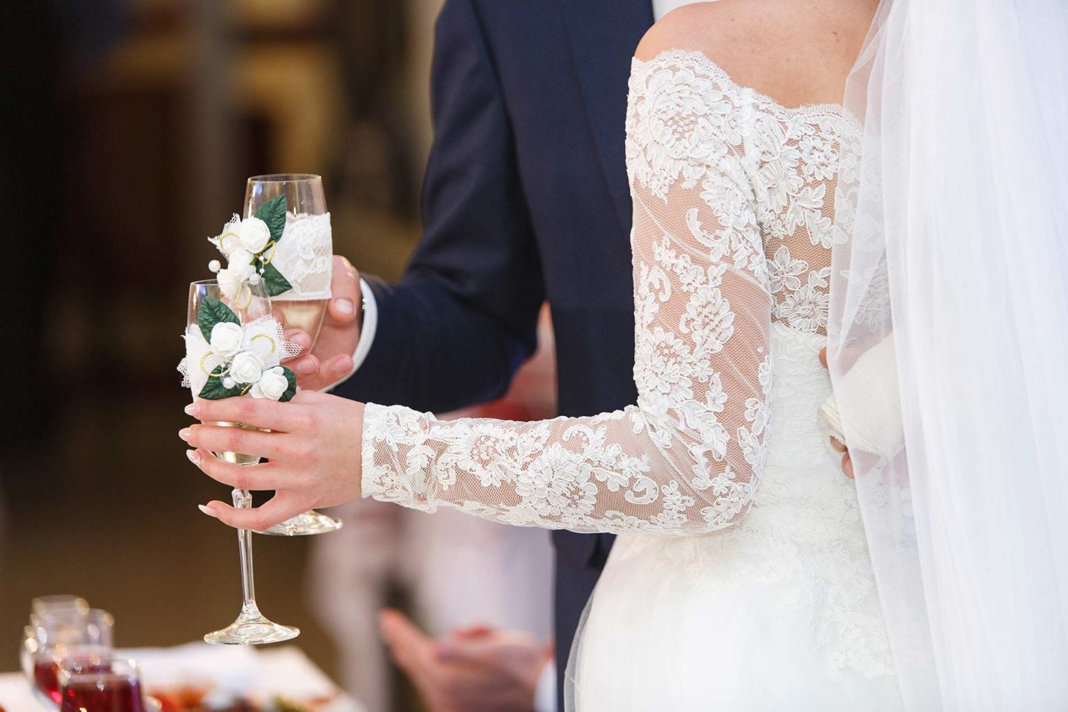 Couple with decorated wine glasses on their wedding day