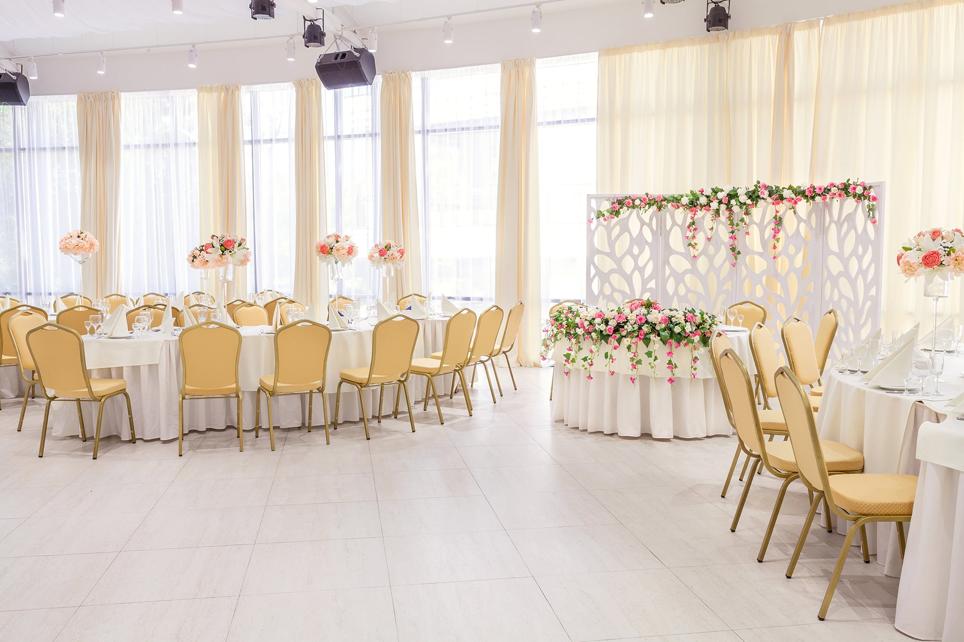 Beautifully decorated room with covered tables with flowers in the restaurant for the celebration of the wedding.