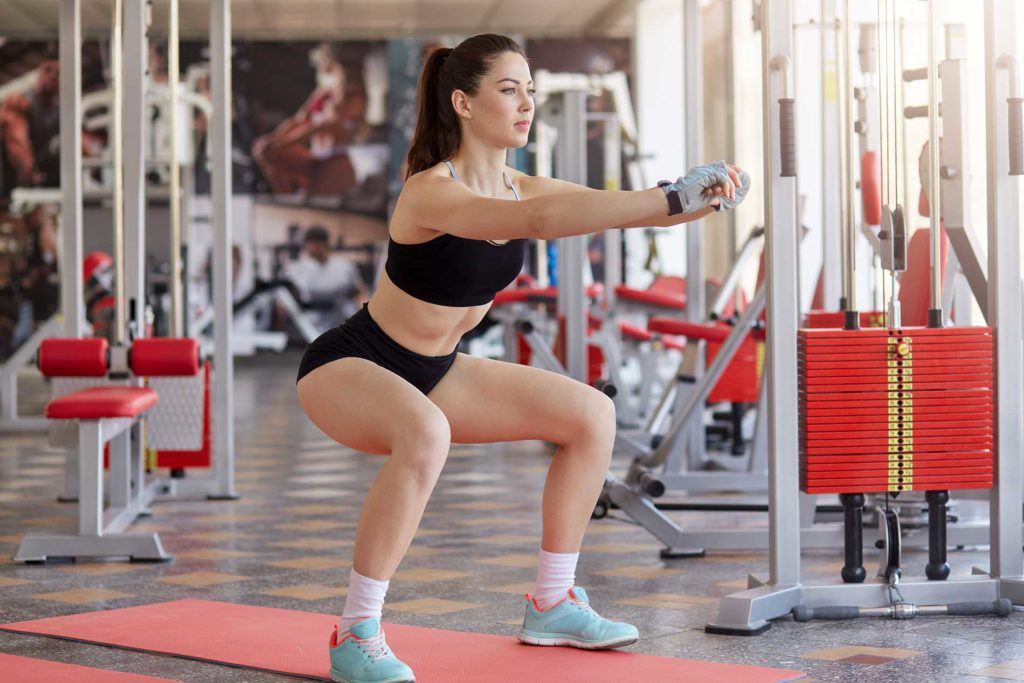 Sporty girl doing squats exercise