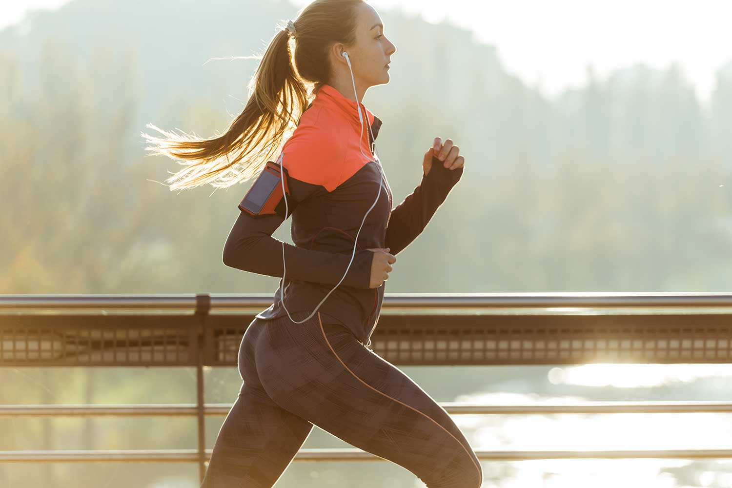 Healthy woman running - hearing music for health while doing exercise