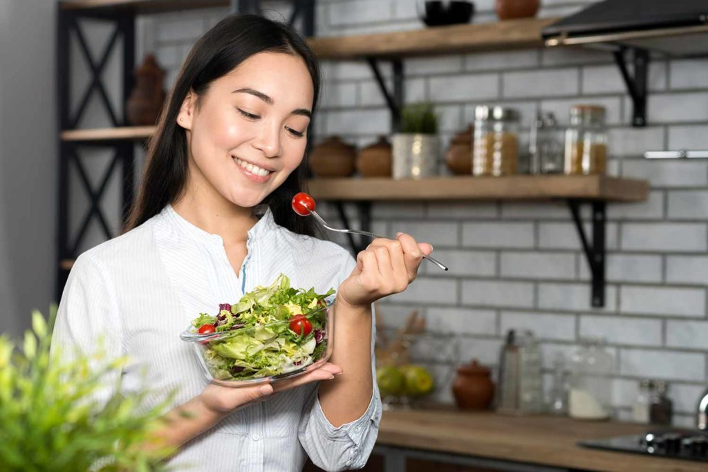 Front view woman eating cherry tomato with green vegetables