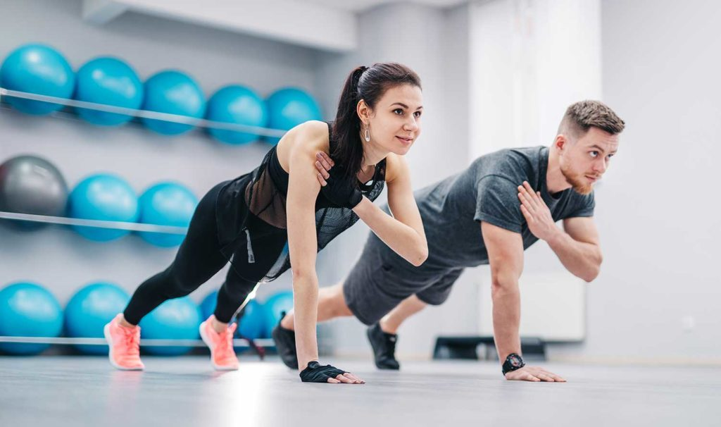 Young couple doing push-ups from floor one hand together