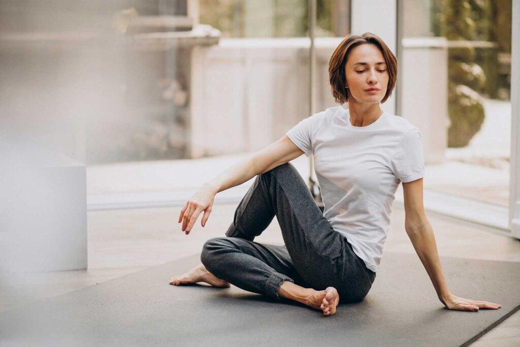 Young woman practicing yoga at home Ardha Matsyendra Asana