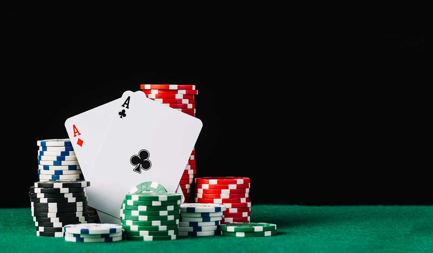 Stack white green black red casino chips with two aces poker table