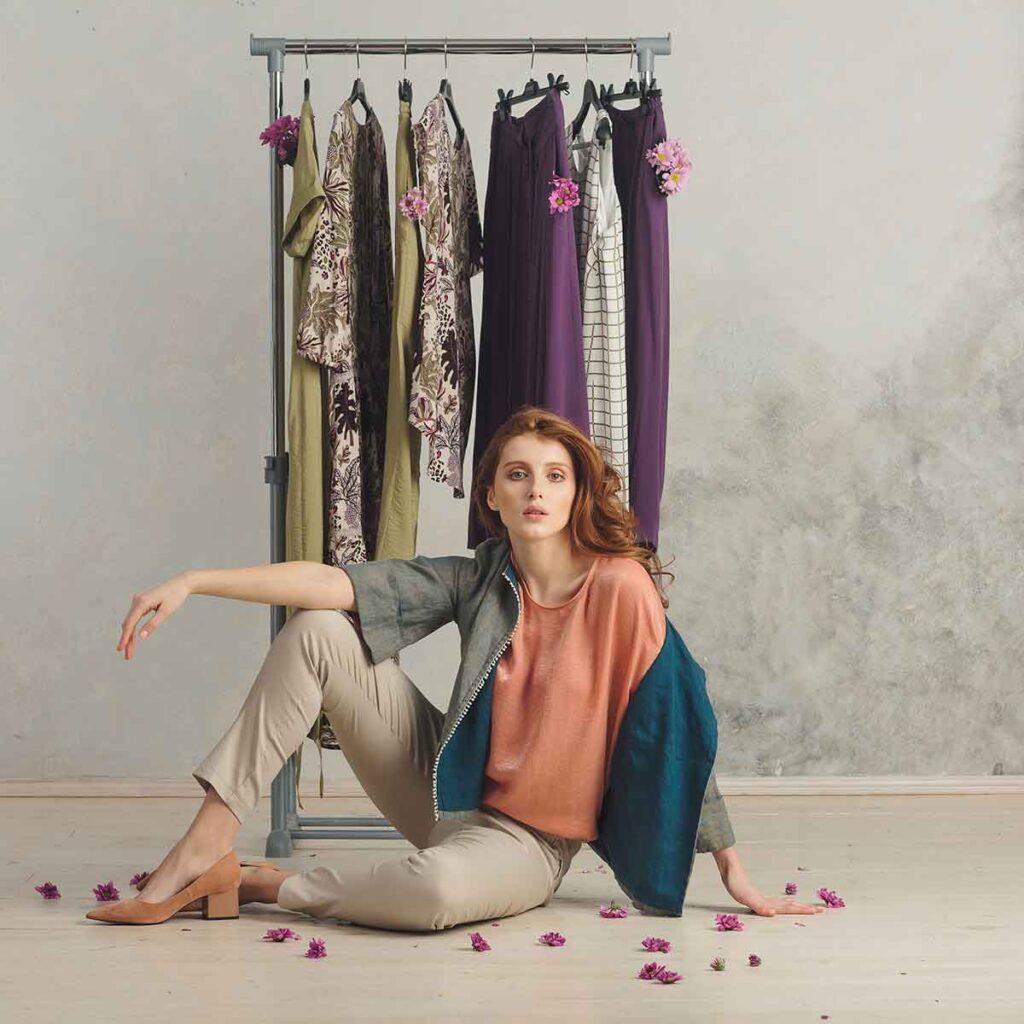 Portrait woman sitting front clothes hanger