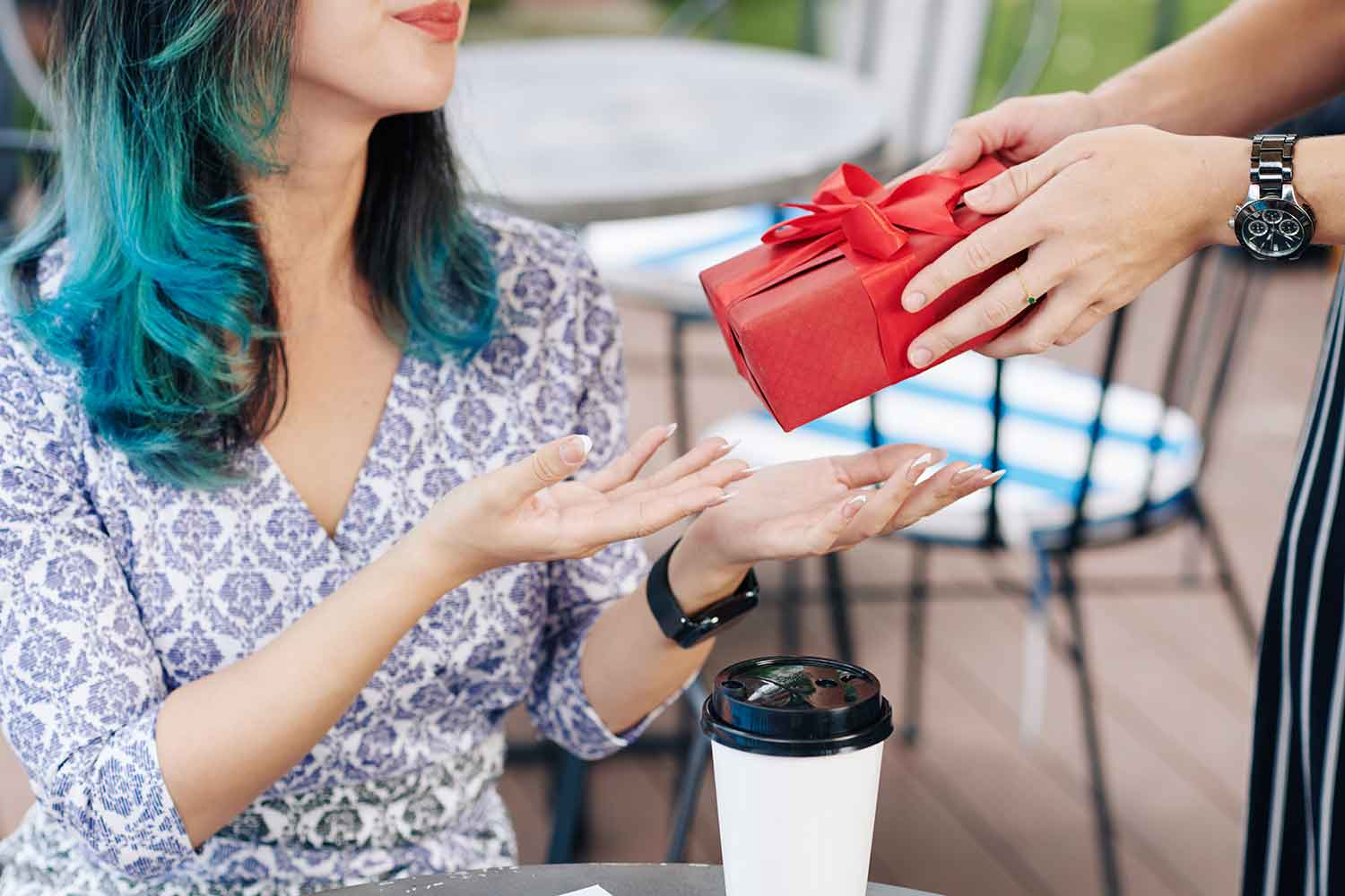 Young woman accepting gift from friend - here are awesome gifting ideas to consider.